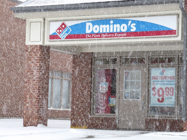 "Domino's Pizza store.  The sign says: ""Domino's, the pizza delivery experts."""
